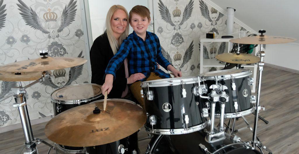 Melanie Junglas mit ihrem Sohn beim Schlagzeug spielen